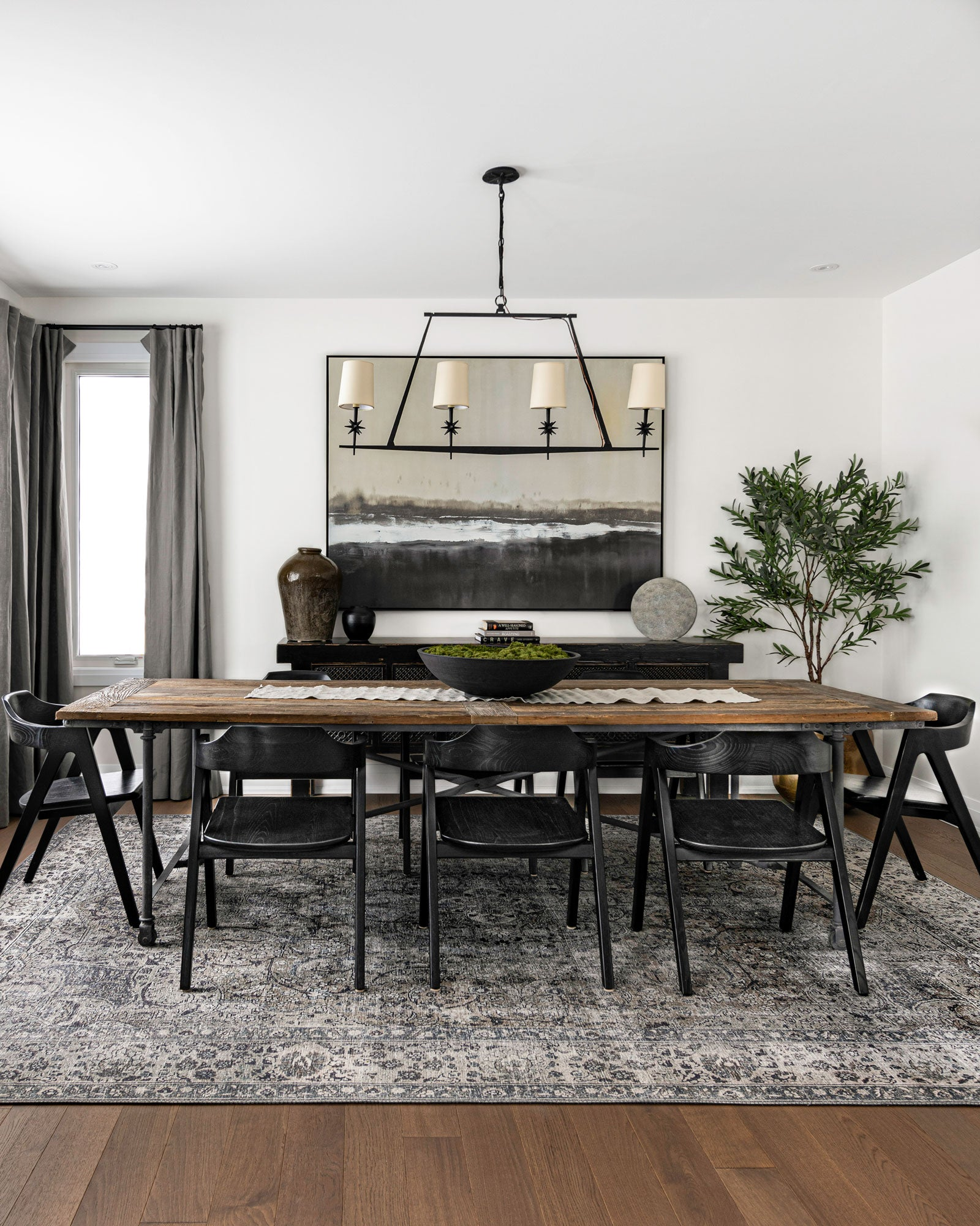 Dining room with large industrial style table and statement chandelier
