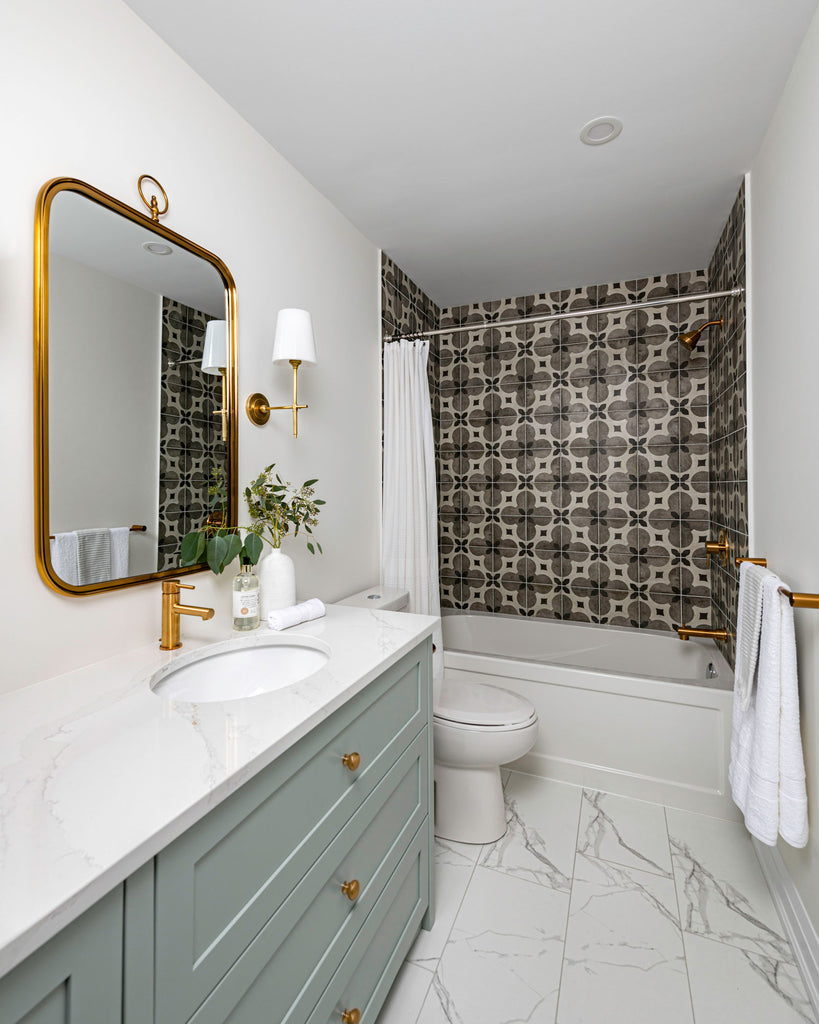 teal bathroom vanity with tiled bathtub and gold accents