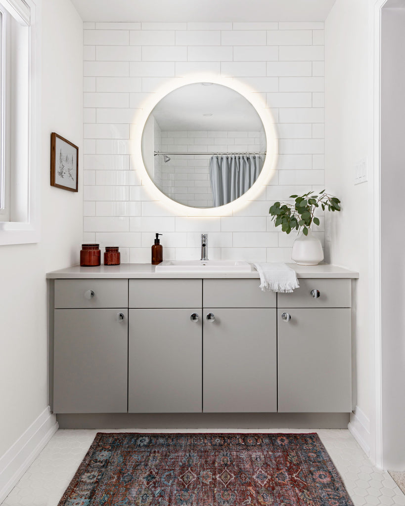 grey bathroom vanity with subway tile backsplash and round mirror