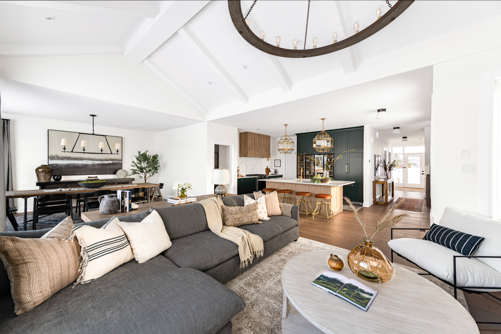 Living room with grey sectional with overview of dining room and kitchen