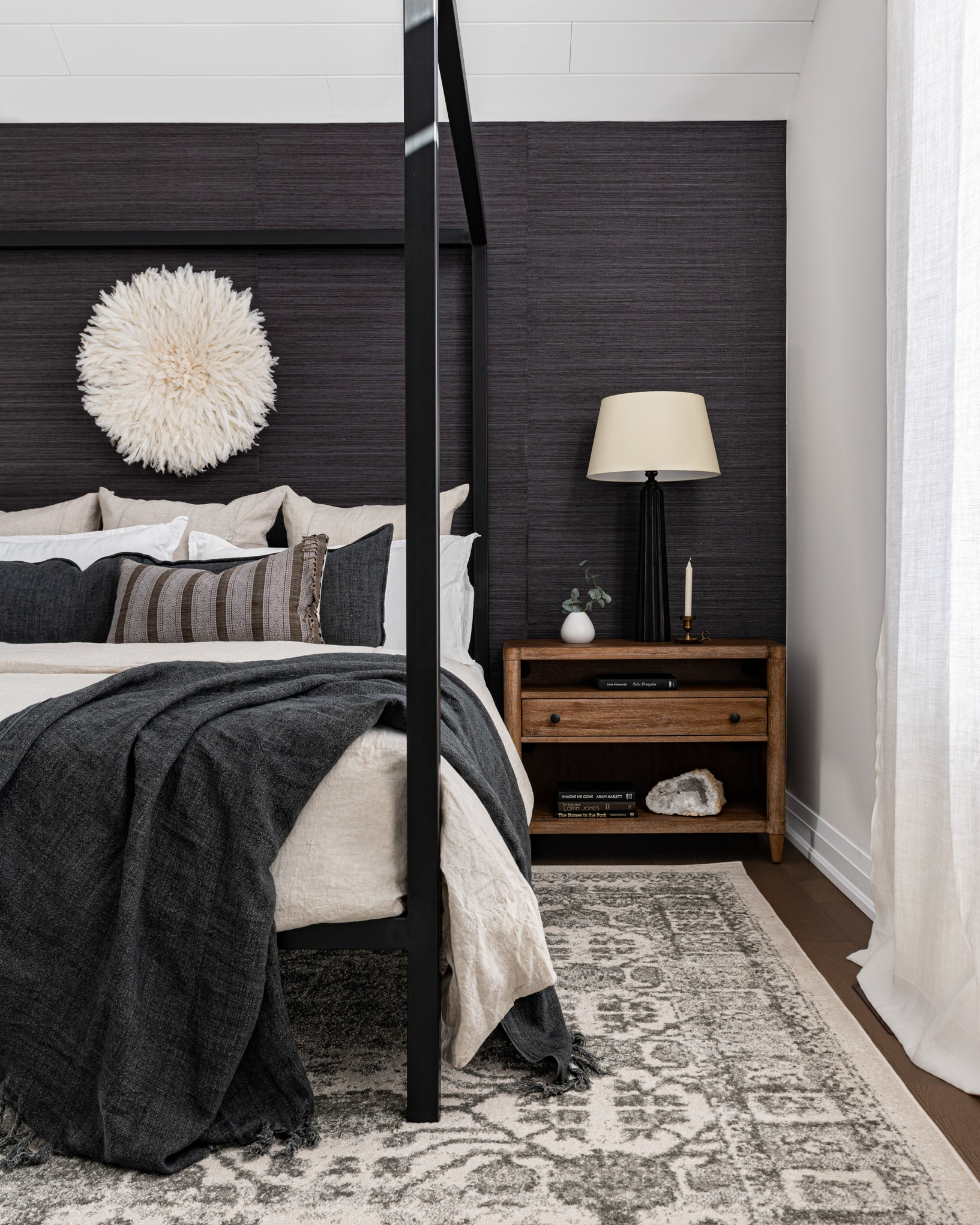 Canopy bed and wood accent in moody master bedroom.