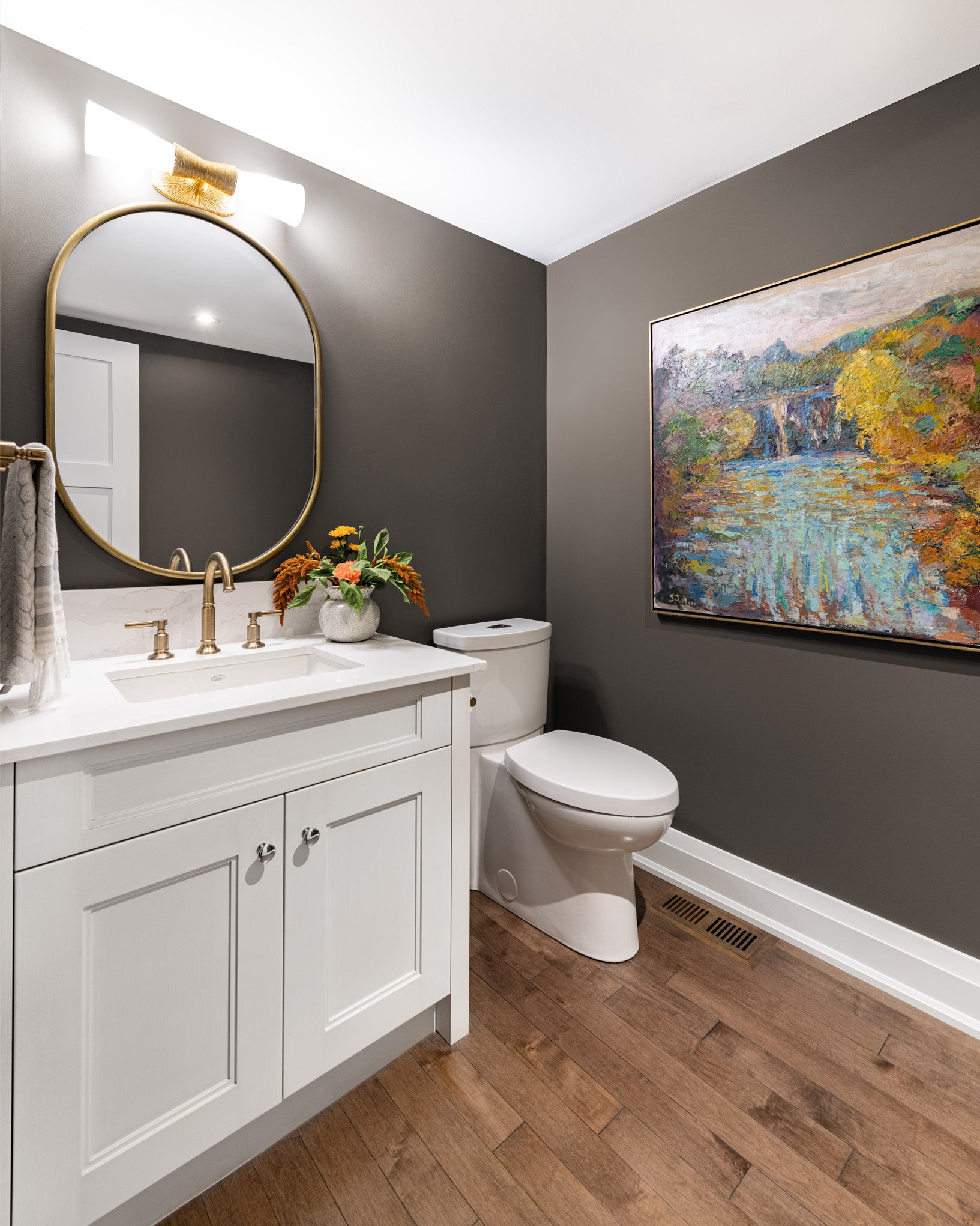 Charcoal powder room with artwork.
