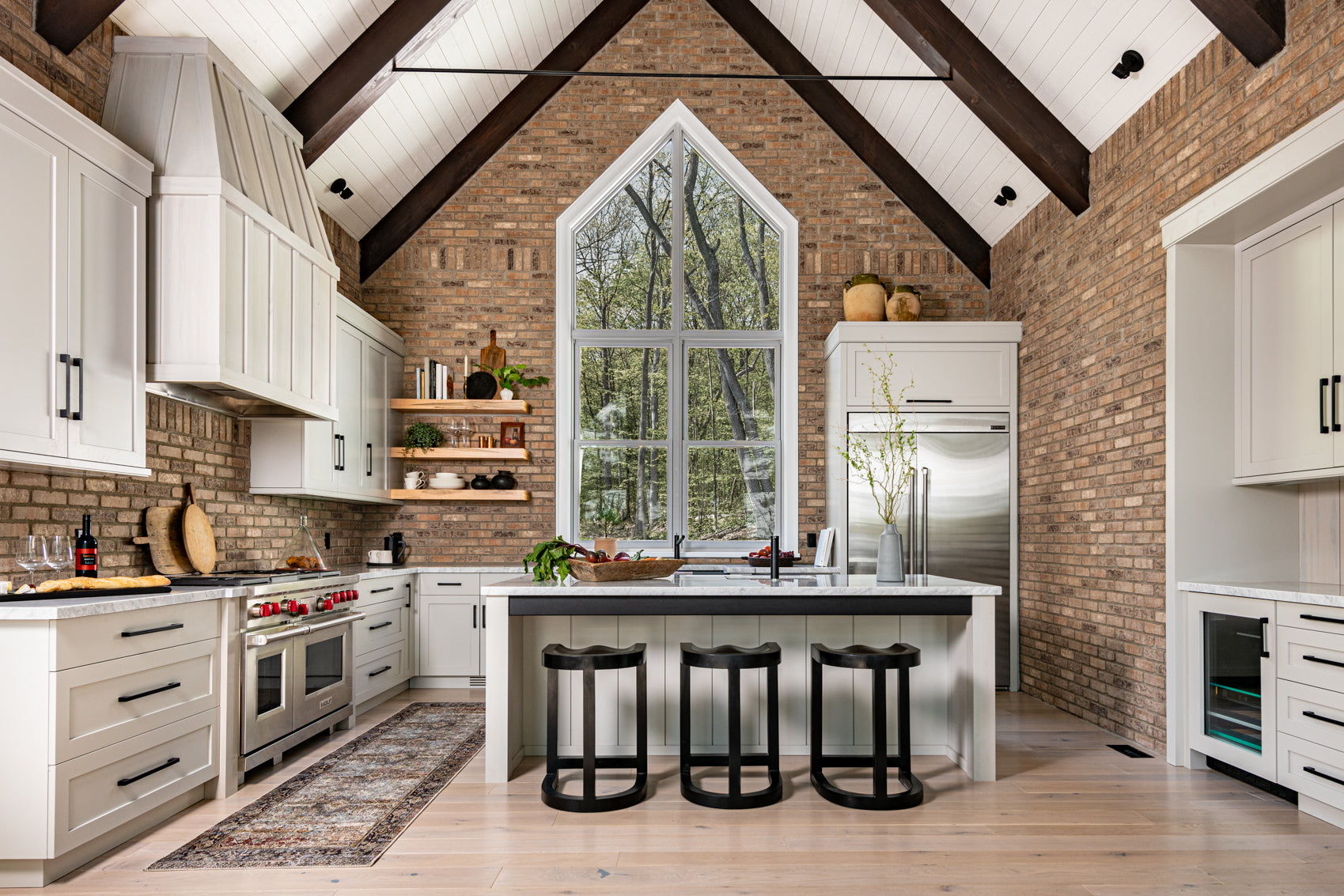 Exposed brick and off white cabinets in kitchen.