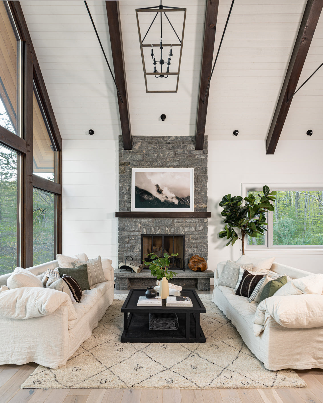 Wooden beams and stone fireplace with white furniture.