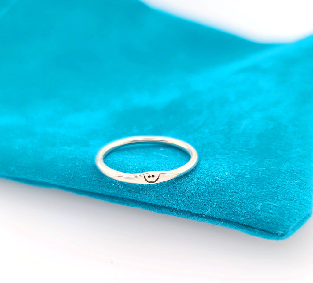small silver ring with smile