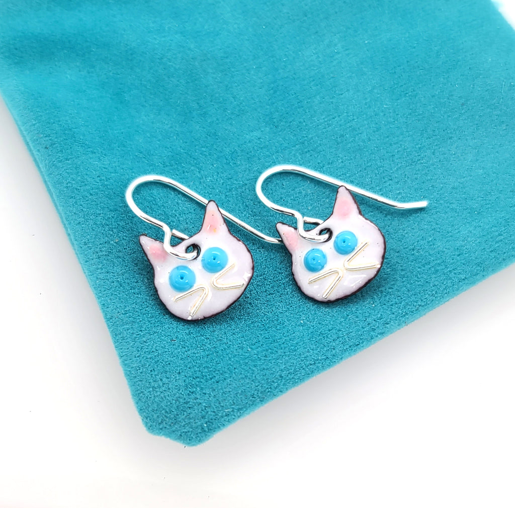 white cat earrings on blue pouch