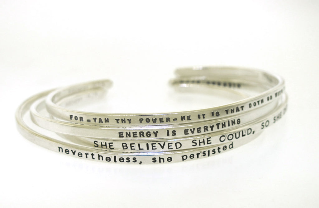 four handstamped silver cuff bracelets with inspirational messages made by kathryn riechert jewelry