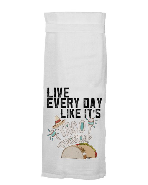 "White kitchen tea towel with the phrase, ""Live every day like it's,"" in all black caps and ""Taco Tuesday"" in bubbly white caps. The T in taco has a tan sombrero on it with two white, teal, and red maracas next to the word ""taco."" and a color illustration of two tacos, one hard, one soft,  underneath."