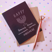 black and white Happy Hanukkah card with a menorah, and the words Happy, with misspelled versions of Hanukkah crossed out with the correct one.