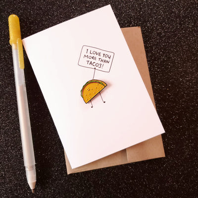 White card with a hard enamel pin of a Kawaii taco, holding a sign on the card, saying