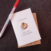 "White card with a soft enamel pin of an orange tabby cat sitting in a cardboard box with a red heart on it, with the words on the card, saying ""I love you like cats loves boxes"""