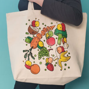 front view of fruits and veggies grocery tote bag being held by female