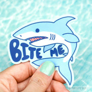 "Shaped sticker of a light blue and white Great White shark with the words, ""Bite me"" in navy blue caps next to the shark."
