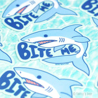 "Several shaped stickers of a light blue and white Great White shark with the words, ""Bite me"" in navy blue caps next to the shark."