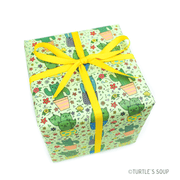 Gift wrapped box with yellow ribbon. Gift wrap has a light green background with Kawaii cat cacti in planters throughout.