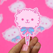 Up closed of shaped sticker featuring a pink cotton candy treat but is also a cat head with a blue bow.