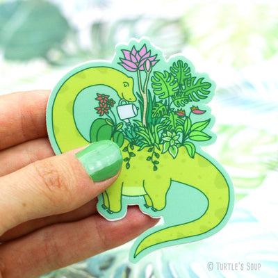Shaped sticker of a green Brontosaurus, that is actually a planter in himself. He is using a watering can and hydrating the plants and flowers growing out of his planter back!