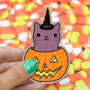 Shaped sticker of a purple-mauve cat with a black witch hat on, coming out of a Jack-o-lantern.