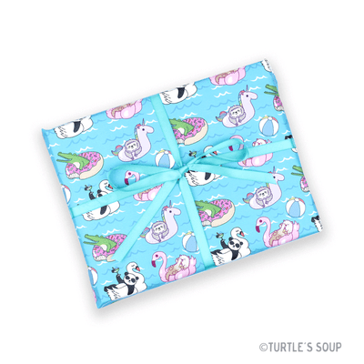 Gift wrapped box with light blue ribbon. Gift wrap has a light blue background with various animals lounging on pool floats. A panda on a swan float, an otter on a flamingo float, a sloth on an unicorn float, and an alligator on a donut float.