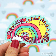 "Shaped sticker of a rainbow and sun, both with Kawaii smiles on them. The words, ""Radiate Positivity"" in rainbow caps, surround the rainbow and sun."