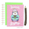 "Holiday card with a pink background with white circle snowflakes. It says 'Season's greetings"" in white cursive and features a purple and white penquin wearing a light blue and pink striped fluffy beanie hat and a light blue/mint sweater. The penquin holds a green present with a red bow and ribbon. A lime green envelope is behind the card with a strip of white washi tape that has green and red candy canes on it, to the left of card and a natural colored pencil to the right."