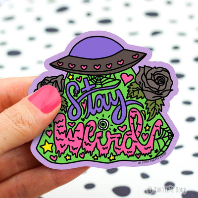 Shaped sticker of a purple and black UFO with a green glow beaming down from it with black roses, cobwebs, hearts, and stars, and the words,