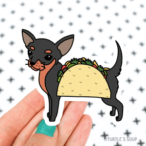 Shaped sticker of black and light brown Chihuahua with a taco in front of him.