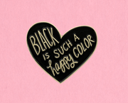 "black heart enamel pin with the words, ""black is such a happy color,"" in gold font."