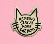gold cat shaped enamel pin with a black outline with the words, Aspiring stay at home cat mom, in the middle, in black font.
