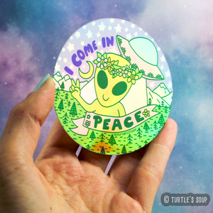 "Round sticker with ""I come in Peace"" in all caps. Alien with a flower head piece on, giving a peace sign, the word Peace is in a pink ribbon under the alien. An UFO is behind the alien and to the upper right of sticker with the ""I come in"" words to the left of it in purple text. Background is of a wooded area with various green trees and grass with white mountains and a starry sky in pastel pinks and purples."