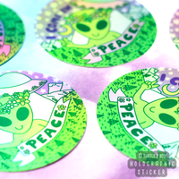 "Three Round stickers with ""I come in Peace"" in all caps. Alien with a flower head piece on, giving a peace sign, the word Peace is in a pink ribbon under the alien. An UFO is behind the alien and to the upper right of sticker with the ""I come in"" words to the left of it in purple text. Background is of a wooded area with various green trees and grass with white mountains and a starry sky in pastel pinks and purples."