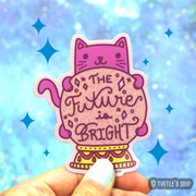 "Shaped sticker of a hot pink cat hugging a glittery light pink crystal ball with that phrase, ""The future is bright"" inside of the future gazing ball."