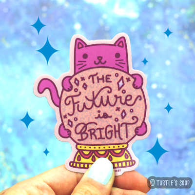 Shaped sticker of a hot pink cat hugging a glittery light pink crystal ball with that phrase,