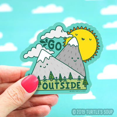 Shaped sticker of two great mountains and a sun behind them, all with Kawaii smiles. Two clouds above the mountains and green grass and various trees below. The words