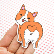 Shaped sticker of a orange-tan and white Corgi puppy, standing with his behind towards you, showing his Corgi-butt, head turned looking back with a tongue out smile!