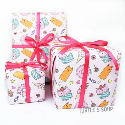 Gift wrapped boxes with pink ribbon. The gift wrap has a light pink background, with various desserts in Kawaii cat form. Donuts, popsicles, cupcakes, ice cream.