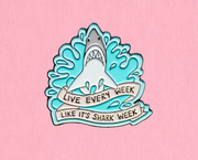 "Enamel pin in pastel blues with a Great White shark splashing up out of the water. A banner underneath it says, ""live every week like it's shark week."""