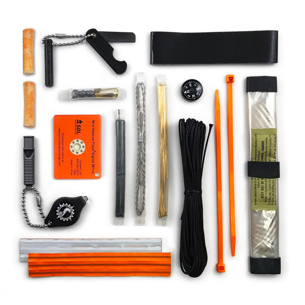 survival kit tools laid out containing signal mirror flashlight knife compass and more