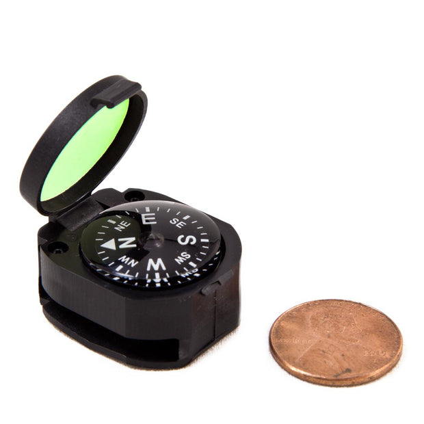 black clamshell container with compass and reflective glow light on the inside of lid compared to the size of a penny that is similar in size