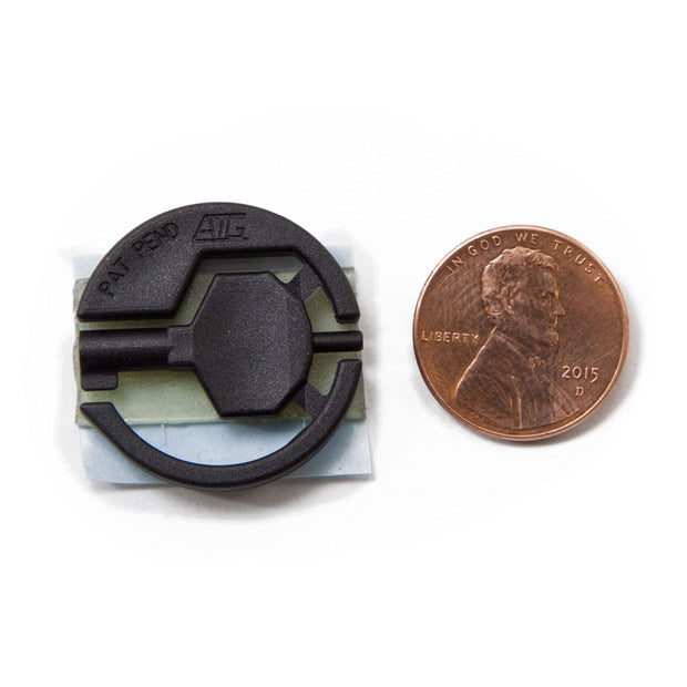 Black handcuff key with adhesive backing attached laid flat next to a penny for size comparison