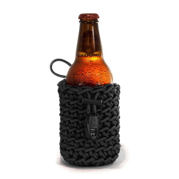 Small black paracord beverage skin pouch with beer bottle inside that comes with attached whistle ferro rod and ceramic scraper