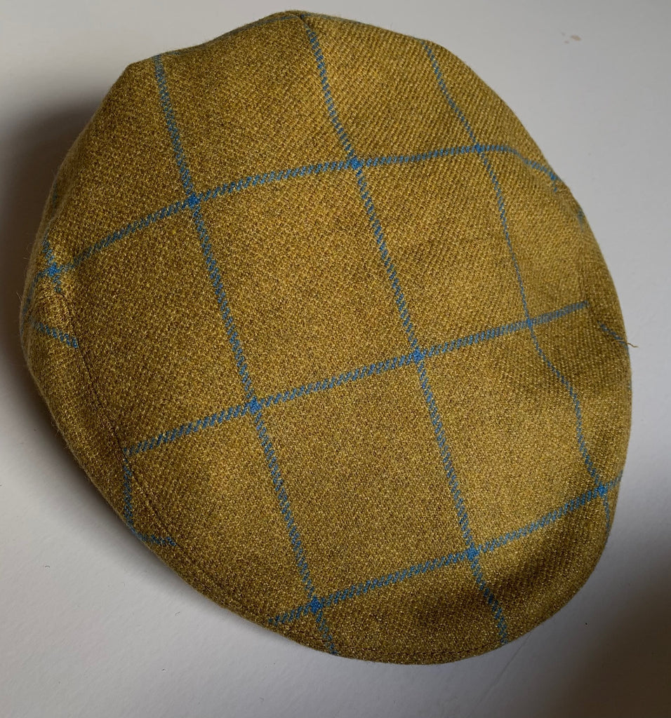 Ochre yellow / burnt gold tweed flat cap with blue overcheck, designed and stocked exclusively by Regent.