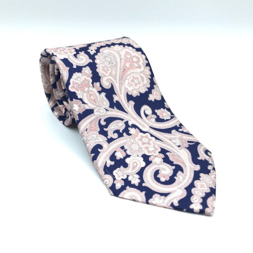 A luxury silk tie designed by and handmade exclusively for Regent. Deep navy is overlaid by royal giant pink paisley pattern.