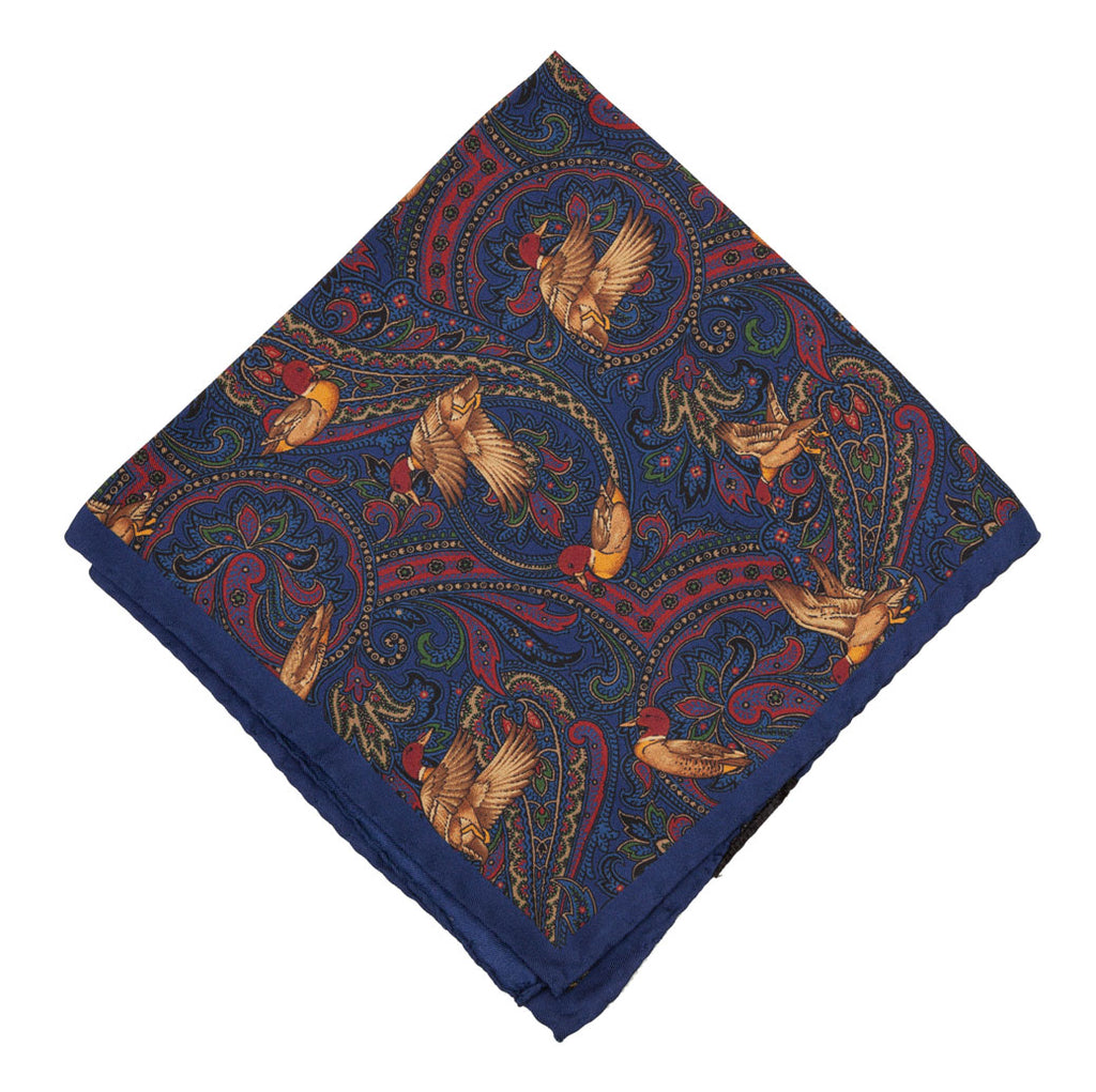 Luxury silk pocket square designed and crafted exclusively for Regent, featuring a dazzling pattern of golden ducks in flight against a night blue.