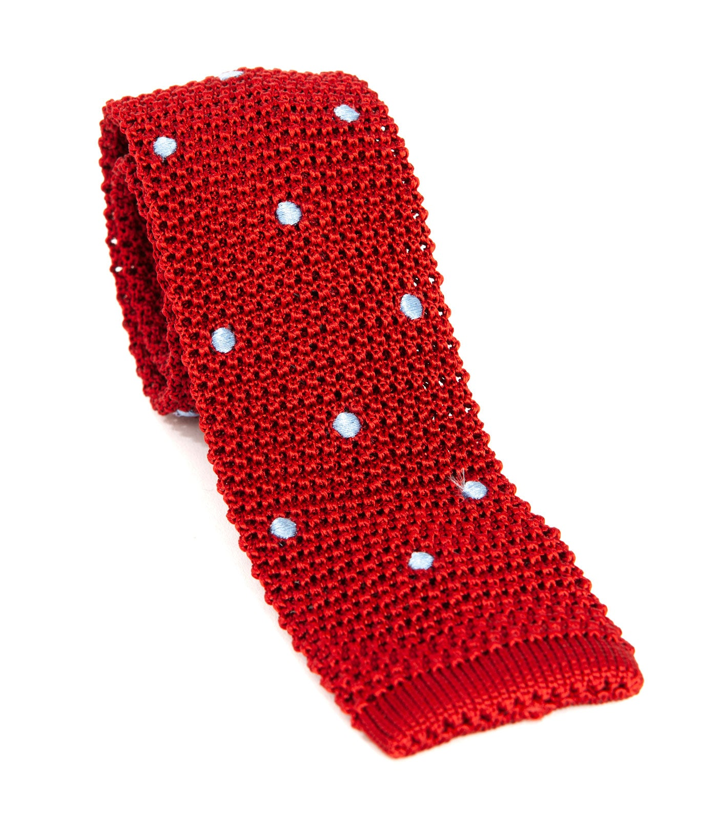 Luxury silk knitted tie designed and made exclusively for Regent. Expertly woven, with a blade width of approximately 5.5cm, this blue-spotted rich red tie from Regent is a unique, playful way to smarten up an outfit.
