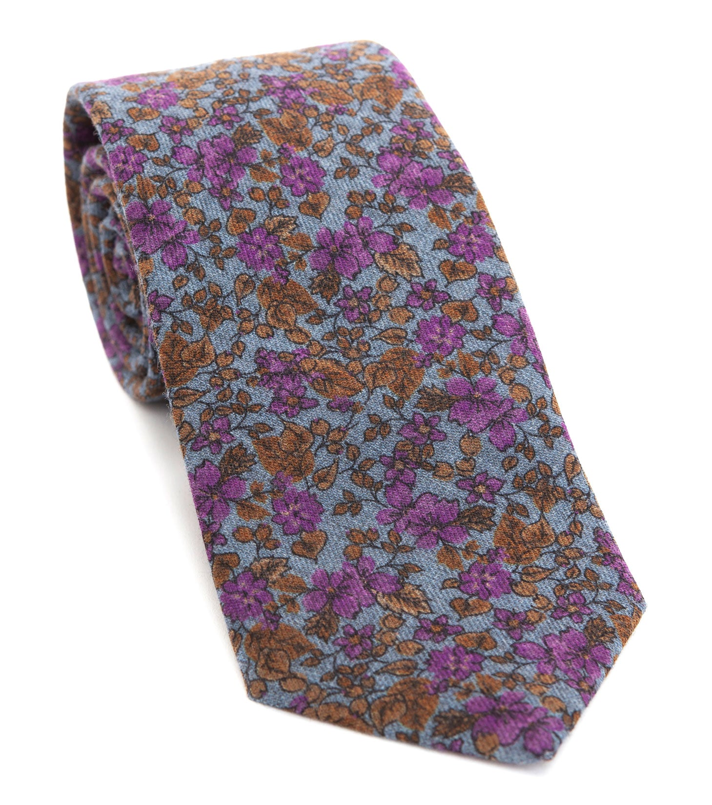 Luxury woven wool tie designed and made exclusively for Regent featuring a soft sky blue overgrown with autumnal gold-brown leaves spurting purple flowers.