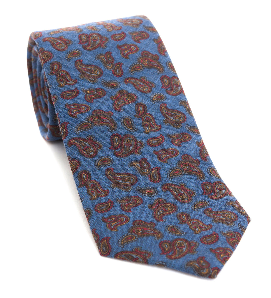 Luxury woven wool tie designed and made exclusively for Regent featuring a deep dusk blue with autumnal red-brown paisley leaves curling through the air of it.