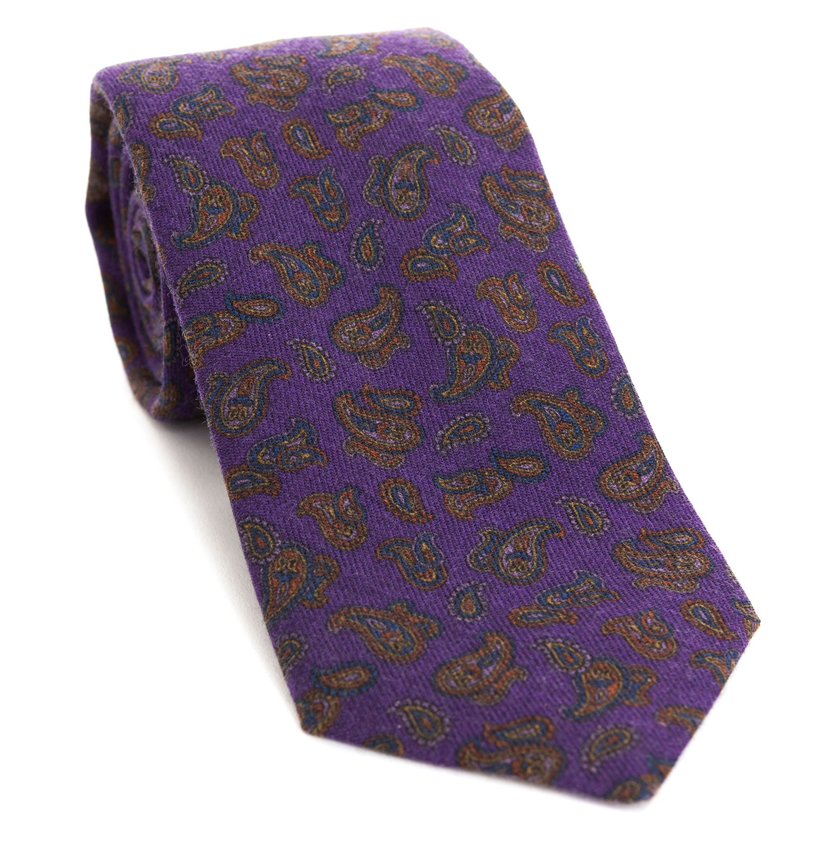Luxury woven wool tie designed and made exclusively for Regent featuring a deep royal purple with autumnal red-brown and blue paisley leaves curling through the air of it.