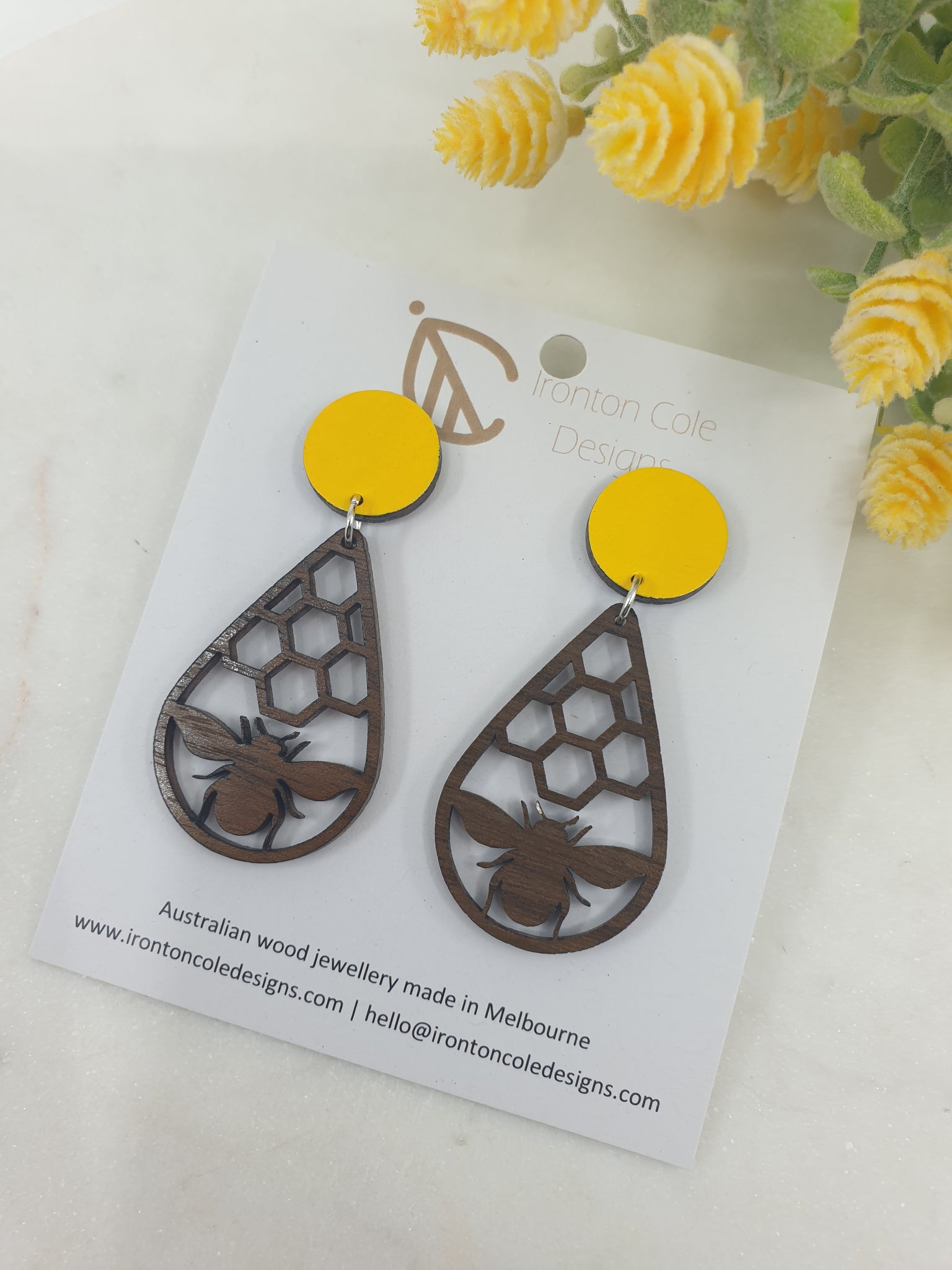 bee and honey comb earrings made from queensland walnut matched with a hand painted yellow disc.