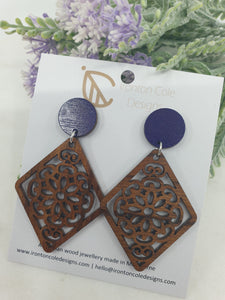 Flower patterned earrings lasered into diamond shaped wooden earrings with paired with a purple disc. hypoallergenic posts.
